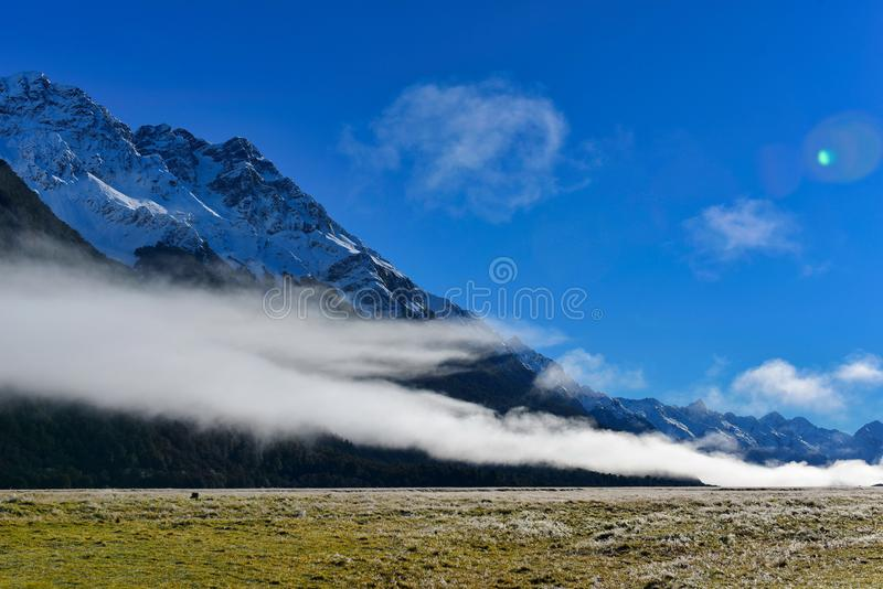White low lying clouds and snow mountains in New Zealand royalty free stock photography