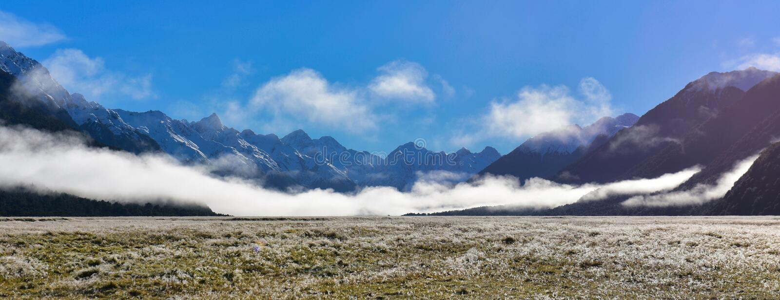 White low lying clouds and snow mountains in New Zealand stock photos