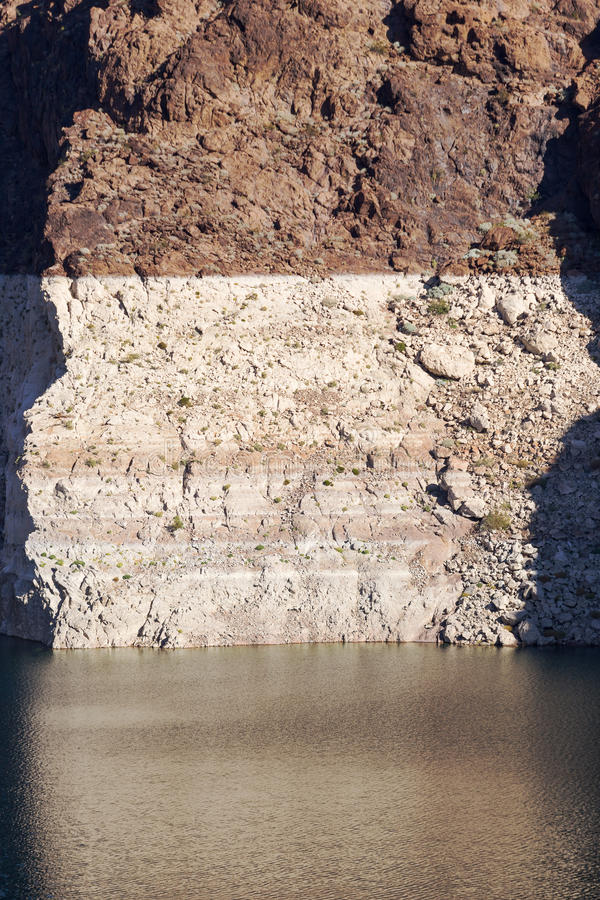 White low water level strip on red cliffs. Of Lake Mead entering Hoover Dam stock images