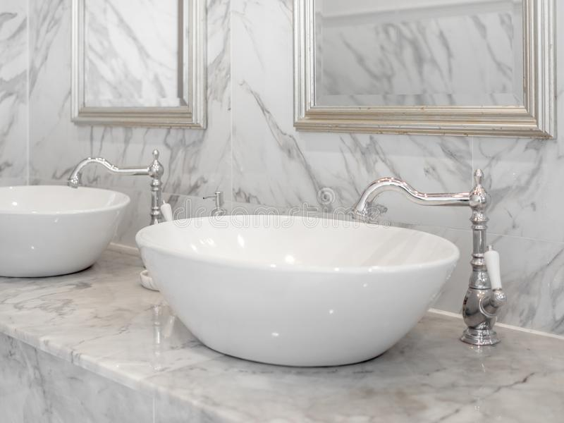 White luxury sink in bathroom. White modern interior design marble bathroom with round wash basin, aluminium faucets and mirrors on the wall stock photo