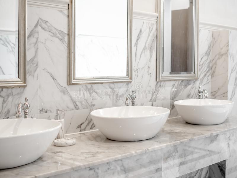 White luxury sink in bathroom. White modern interior design marble bathroom with three round wash basin, aluminium faucets and mirrors on the wall royalty free stock photos