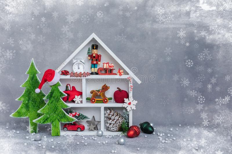 White winter magical wooden cupboard with christmas toys and presents, cone, alarm clock, branches of fir-tree, postcard royalty free stock images