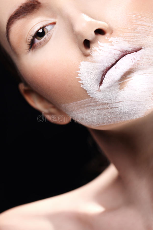 White makeup. Portrait of a beautiful woman with lips painted over with white paint stock image
