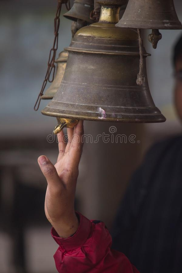 A white male hand rings a temple bell stock images