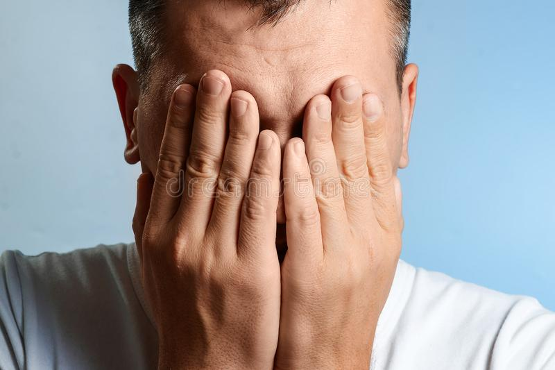 White man, close-up portrait, covered his face with his hands on a blue background stock photo