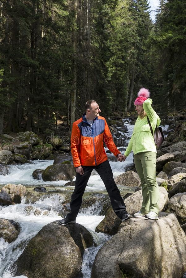 White man and woman standing on the rocks on the Bank of a mountain river in the spruce forest, people in nature royalty free stock image