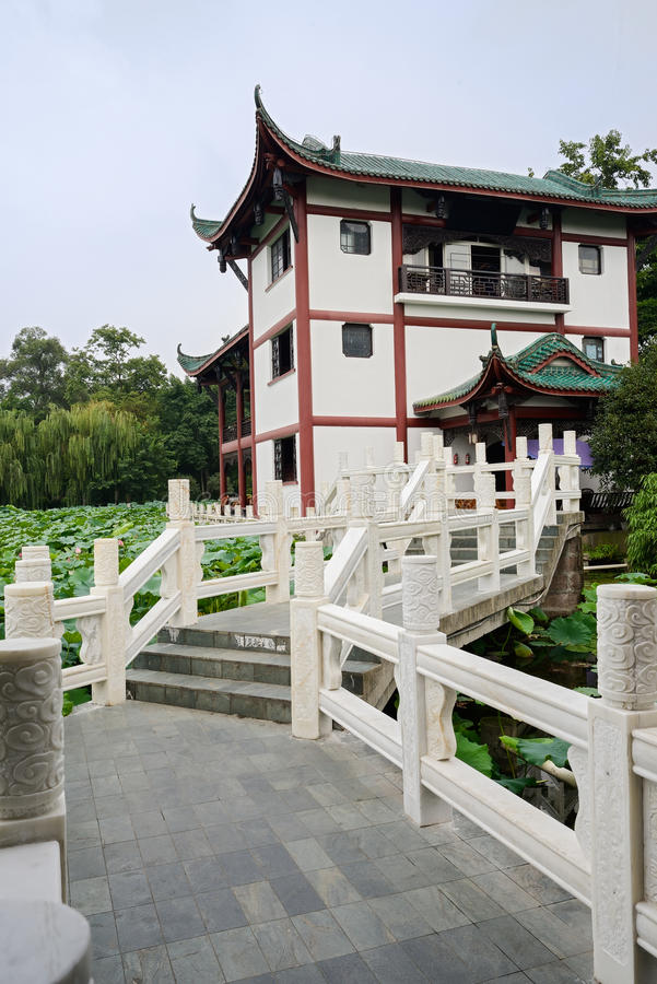 White marble bridge before Chinese traditional building. A bridge with white marble balustrades leads to the building in Chinese traditional style on sunny stock photos
