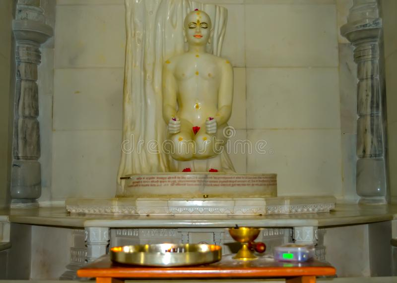 White marble sculpture of Jain tirthankara in meditation. In daytime inside jain temple. Image is inspiring and calm be used as a background, wallpaper, screen stock photos