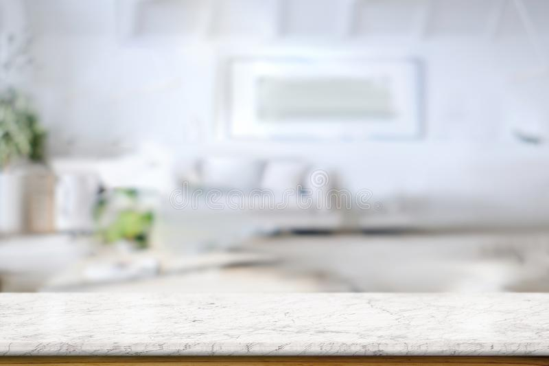 White marble table top over living room at home. White marble table top with blur of modern living room interior as background stock photos