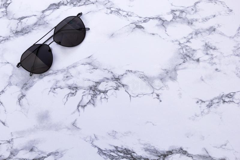 White marble texture with black sunglasses and background for design pattern artwork, modern concept of natural organic trend royalty free stock photography