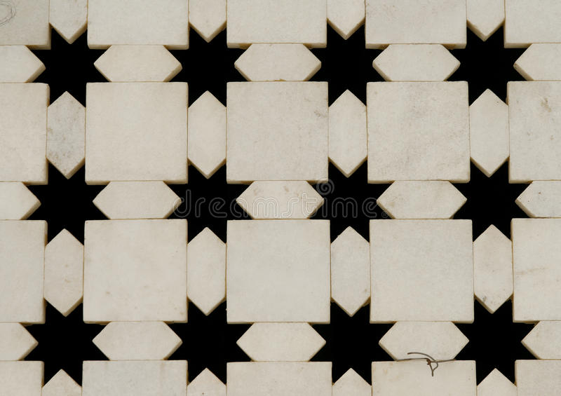 White marble wall with star shape cut-outs. India. White marble wall with star shape cut-outs. Close-up of Jaigurudeo Temple wall, India stock image