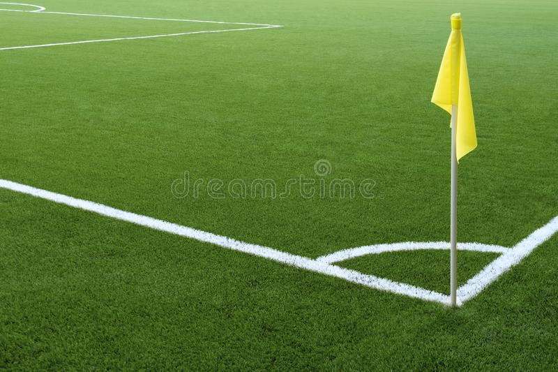 Corner of a football field. White markings on green grass and yellow flag. No people and players. Sports concept royalty free stock image