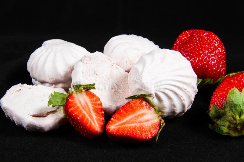 White marshmallows, red strawberries, black background. royalty free stock photo
