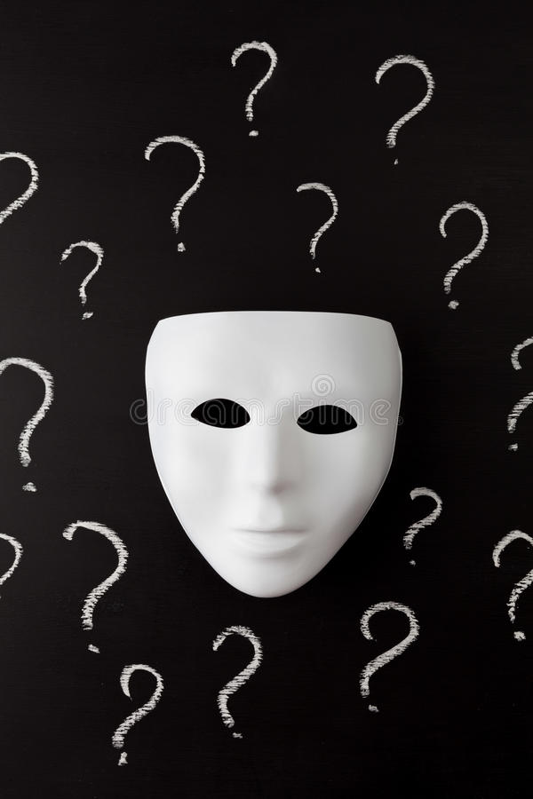 White mask on black with question marks vertical stock image