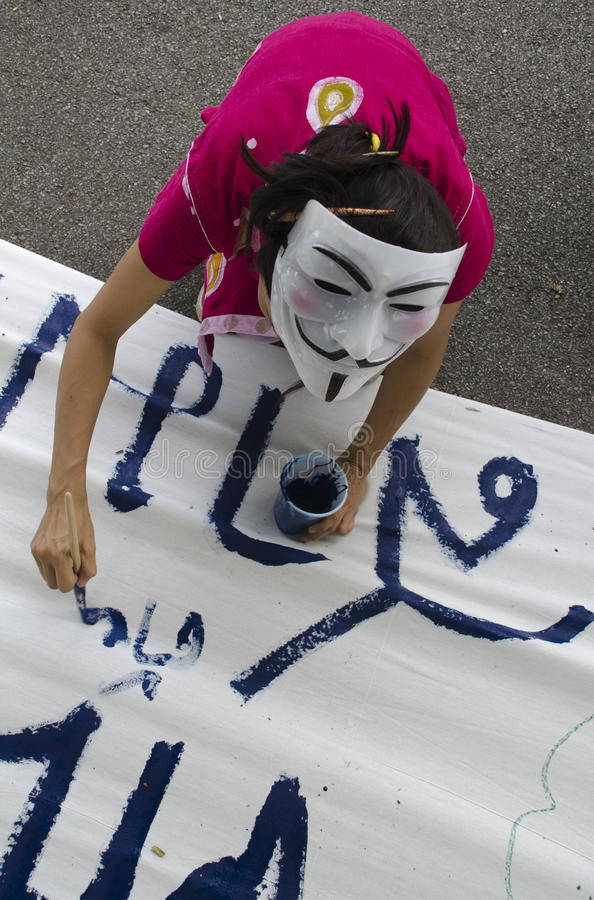 White Mask Protestor Paints On Banner Editorial Image