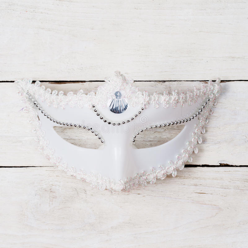 White mask. On a wooden background with copy space royalty free stock images