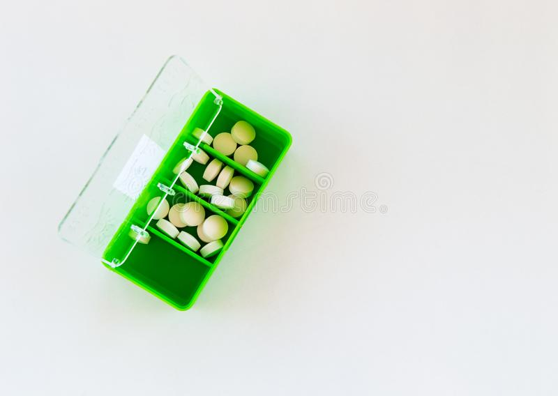 White medical pills in a green medication box. Top view with copy space. royalty free stock photos