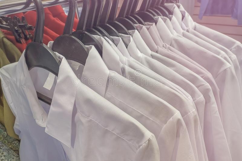 White men`s shirts on hangers. Clothes on display stock photos