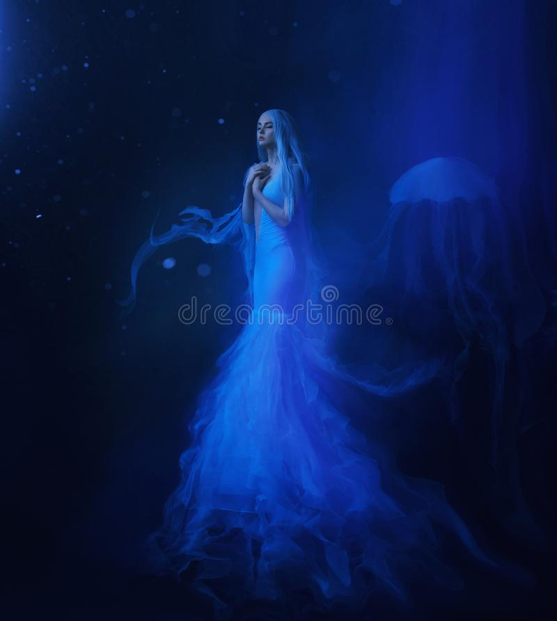 A white mermaid, with very long and blue hair floating under the water. An unusual image, the tail of a jellyfish. Levitation and weightlessness. Pale skin stock photography