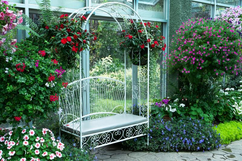 White metal arch bench in indoor park in the Royal flora public garden in Chiangmai, stock photography