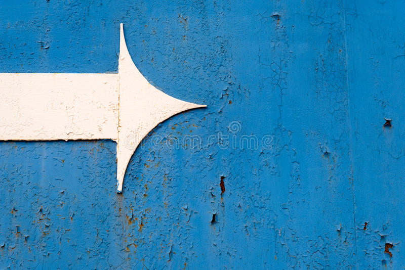White Metal Arrow on Rusted Blue Metal royalty free stock images