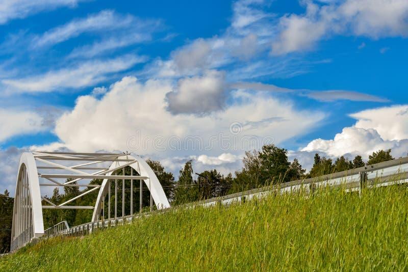 White metal bridge. Sunny, day, summer, blue, sky, field, green, grass, trees, forest, road, sweden, rural, scandinavia, landscape, travel, tourism stock image