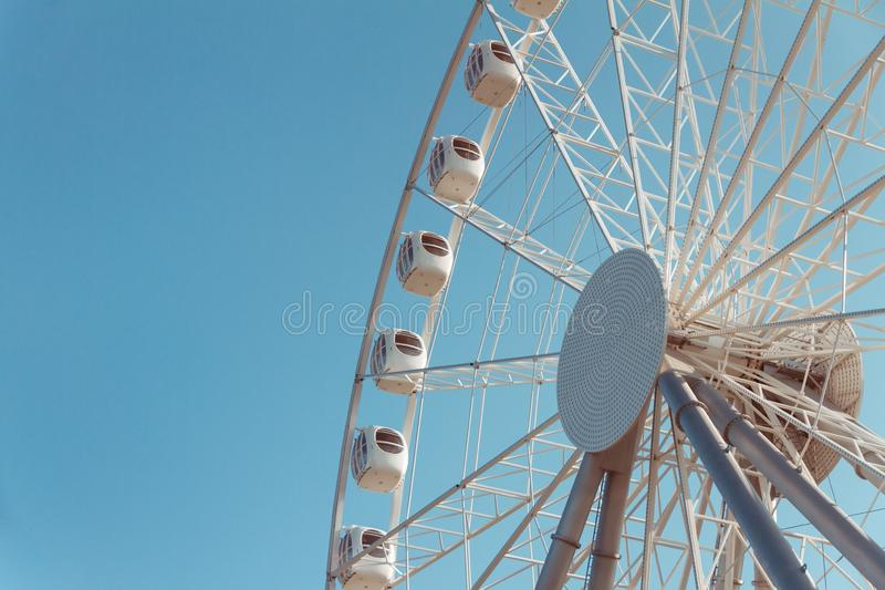 White metal cabins of ferris wheel with booths with windows against blue sky, bottom view. Half of white metal review wheel with booths with windows against blue stock images