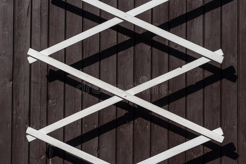 White metal lattice on a wooden wall. Of a cottage royalty free stock images