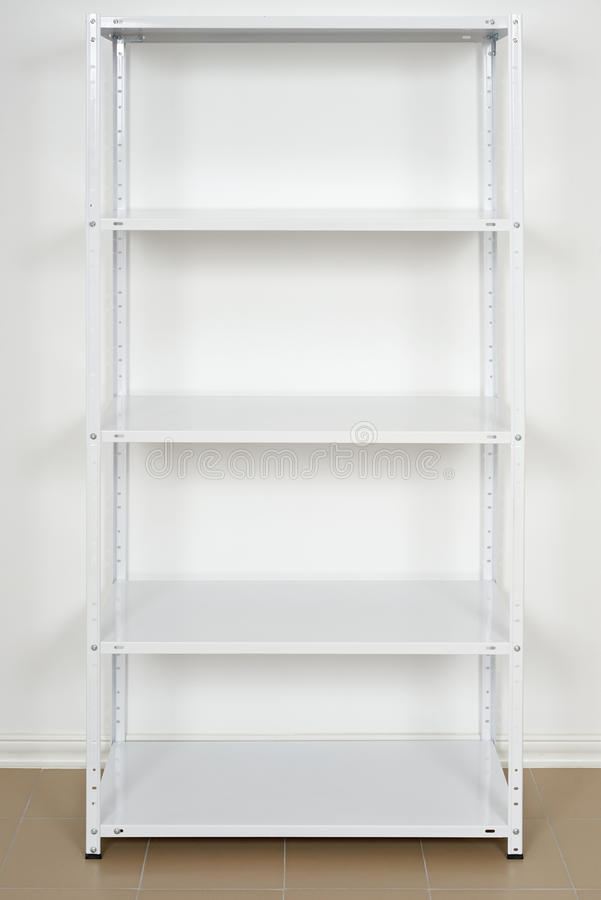 White metal rack near the wall, empty shelves royalty free stock image