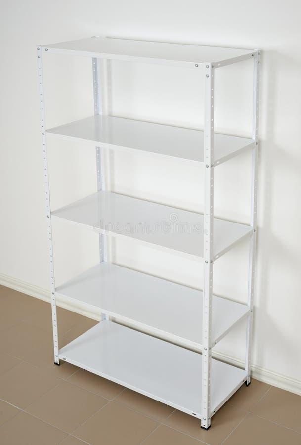 White metal rack near the wall, empty shelves royalty free stock photos