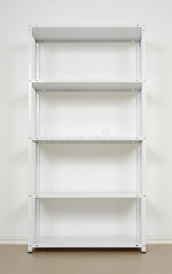White metal rack near the wall, empty shelves stock photo