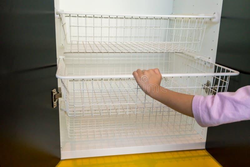 White metal rack shelves inside the modern wooden cabinet. Kid`s hand open white metal rack shelves inside the modern wooden cabinet on yellow floor stock image