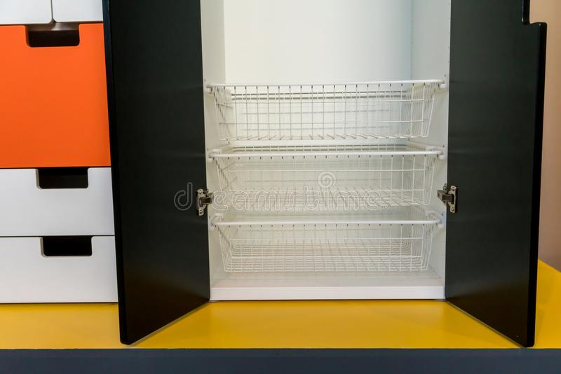 White metal rack shelves inside the modern wooden cabinet. On yellow floor royalty free stock photos