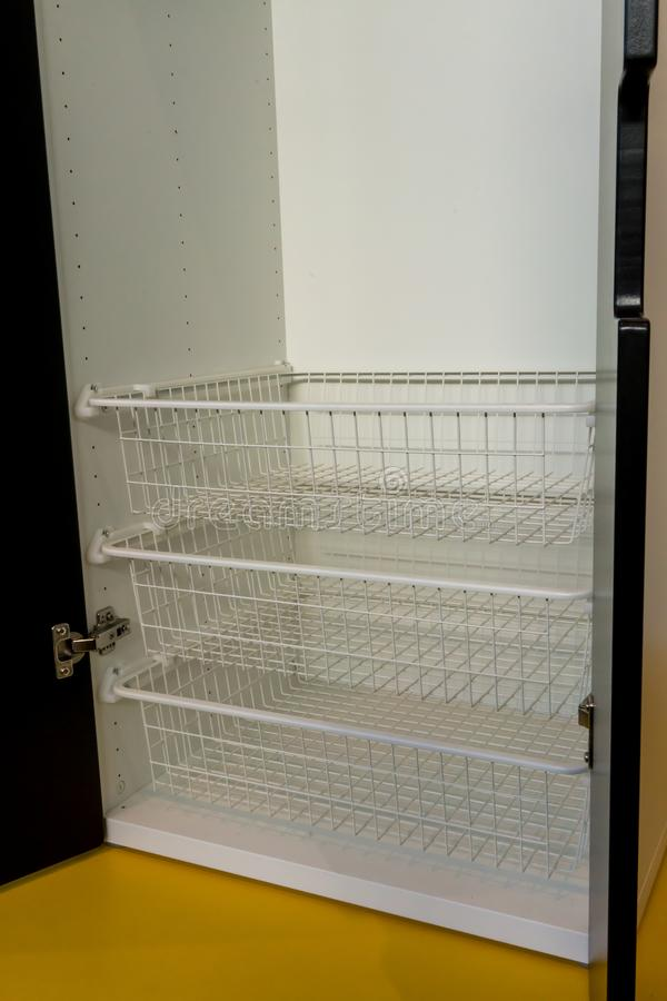 White metal rack shelves inside the modern wooden cabinet. On yellow floor royalty free stock photo