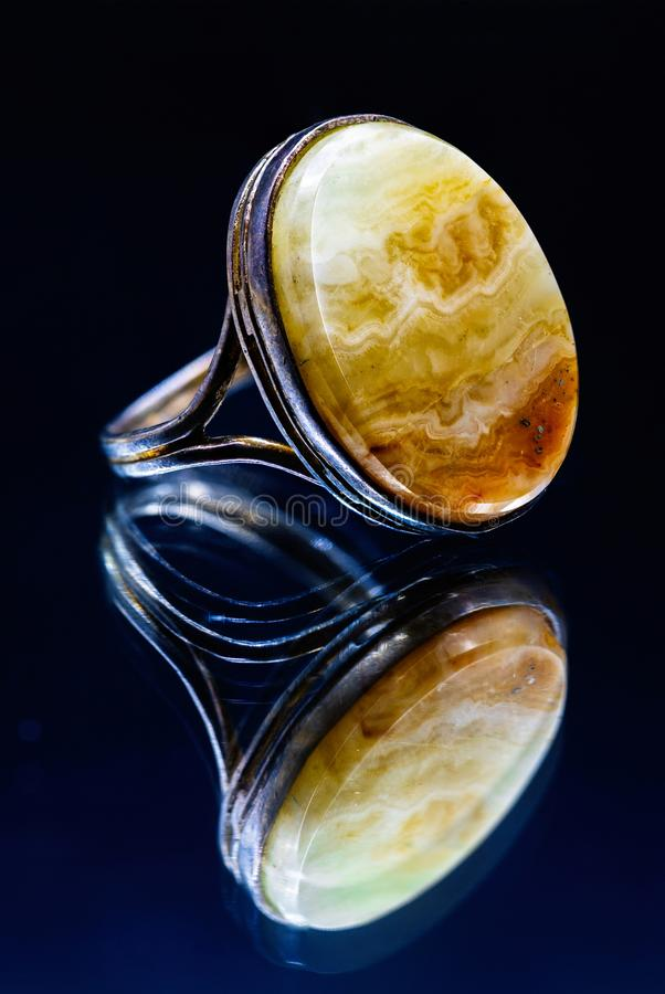 White metal ring with big amber stone reflection royalty free stock image