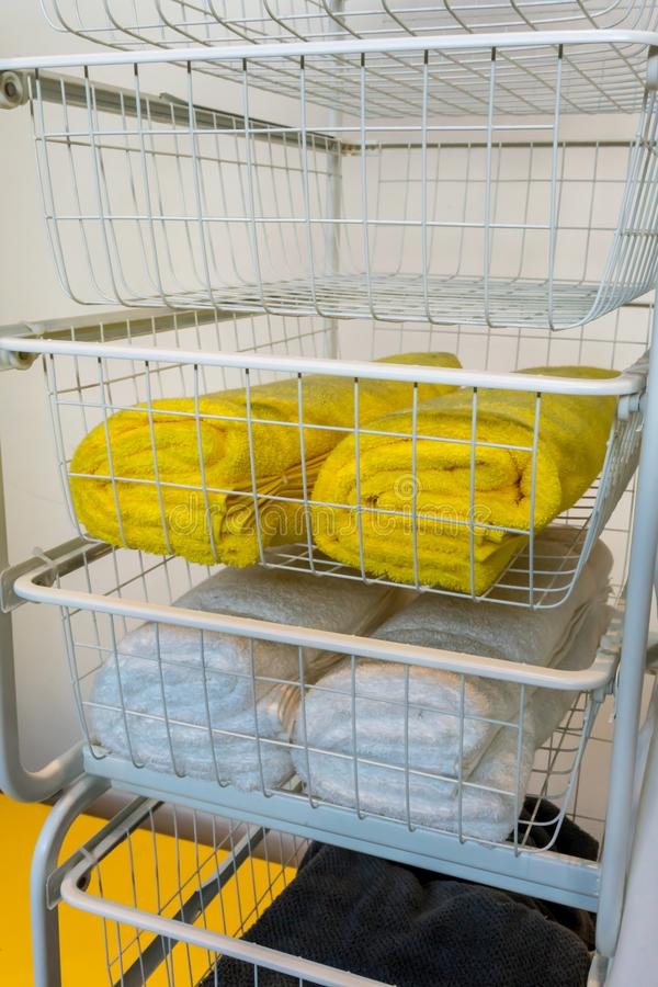 White metal shelve rack with yellow, white and dark grey towel royalty free stock image
