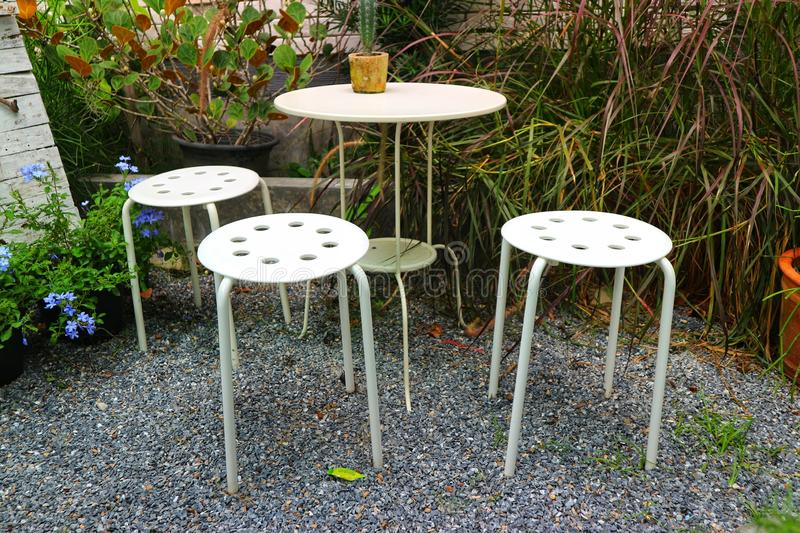 White metal table and chair furniture, modern design in the garden royalty free stock images