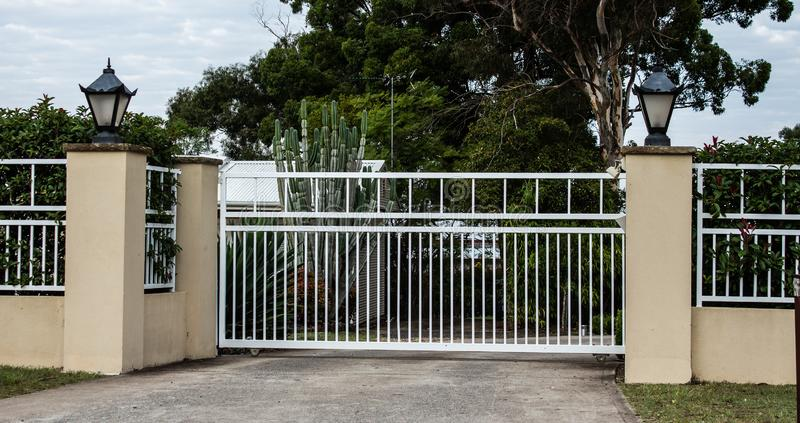 White metal wrought iron driveway property entrance gates set in concrete brick fence with coach lights, garden shrubs and trees i. White wrought iron driveway stock images