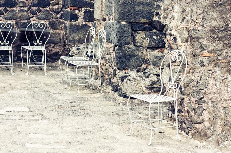 White metall chairs in the yard of castle Acicastello, Acitrezza, Catania, Sicily, Italy.  stock image