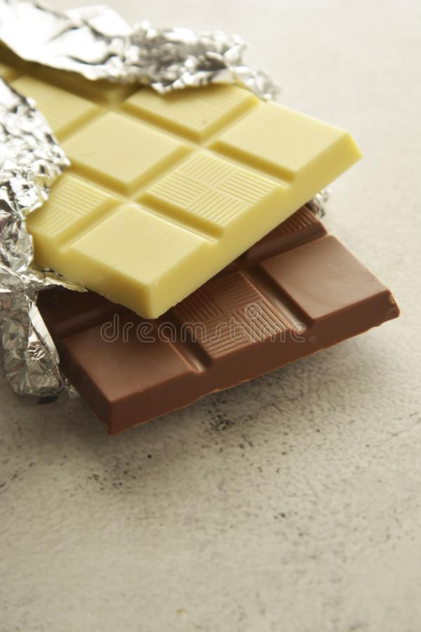 White and milk chocolate isolated. Top view of various chocolate bars with copy space. White and milk chocolate isolated. Top view of various chocolate bars stock images