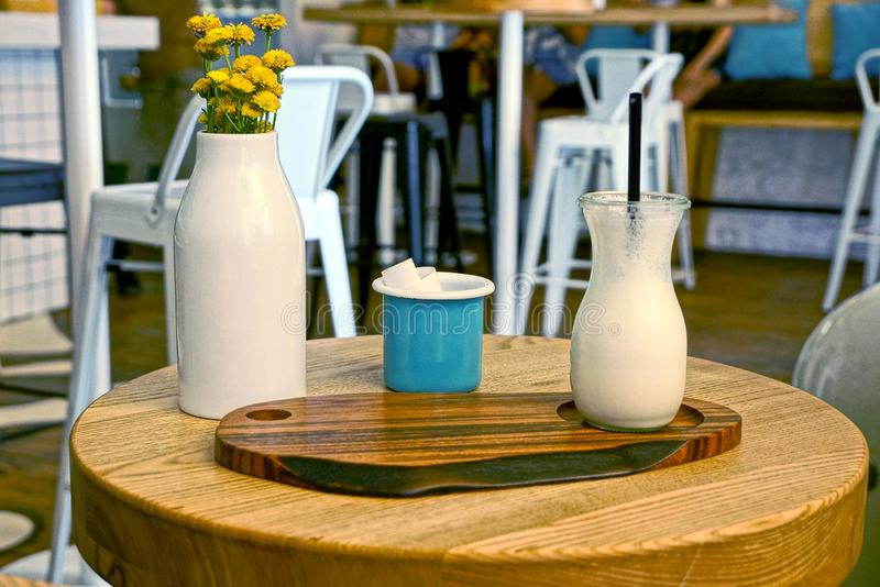 White milkshake in a glass bottle on a brown wooden table with a cup and flowerpot with yellow flowers. In the restaurant room stock photo