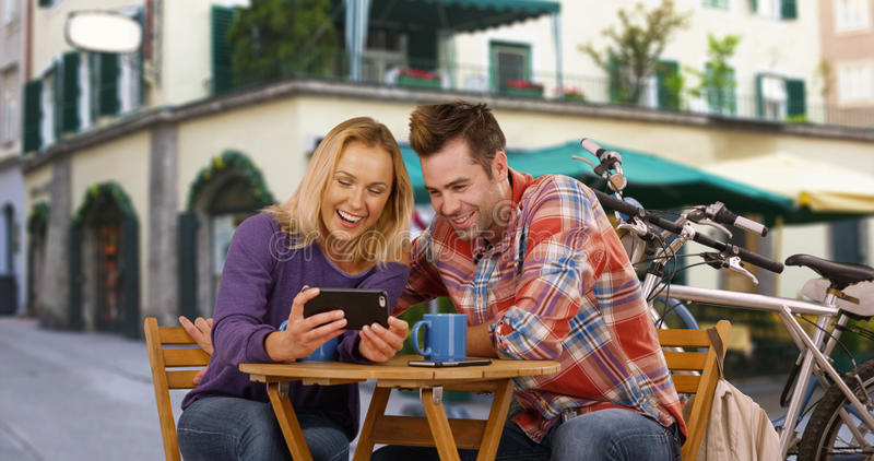 White millennial couple laughing and having a good time outside a coffee shop royalty free stock photos