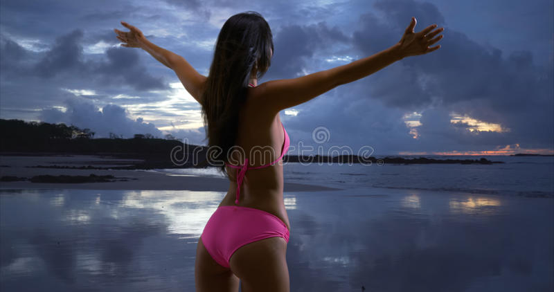 White millennial female looks out onto the stormy sunset on the beaches of St John.  royalty free stock images