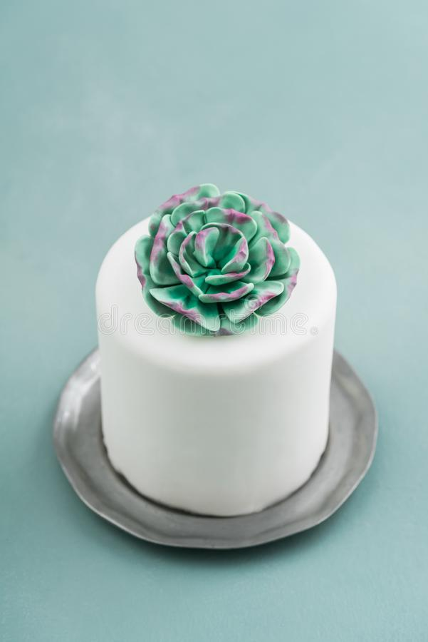 Mini succulent wedding cake. White mini wedding cake covered with fondant with gum paste succulent on a pewter plate stock photos