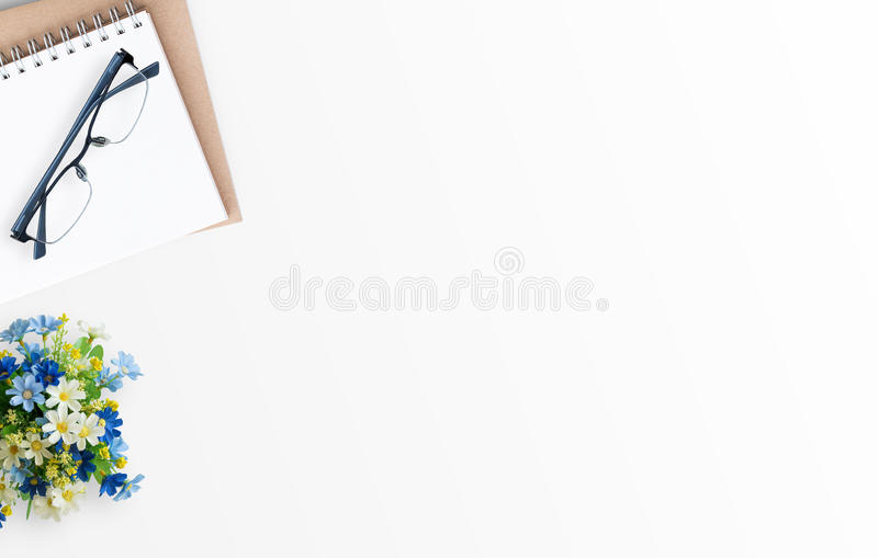 White minimal office desk table with notebook,glasses and flower royalty free stock photos