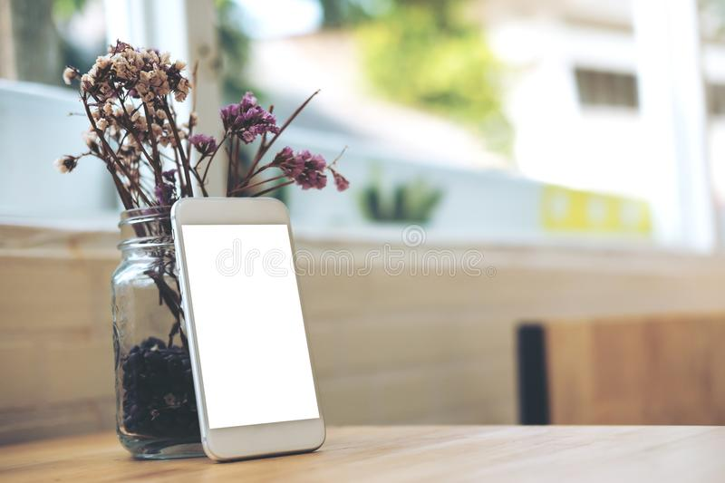 White mobile phone with blank white screen with flower vase on wooden table in modern cafe. Mockup image of white mobile phone with blank white screen with stock photos
