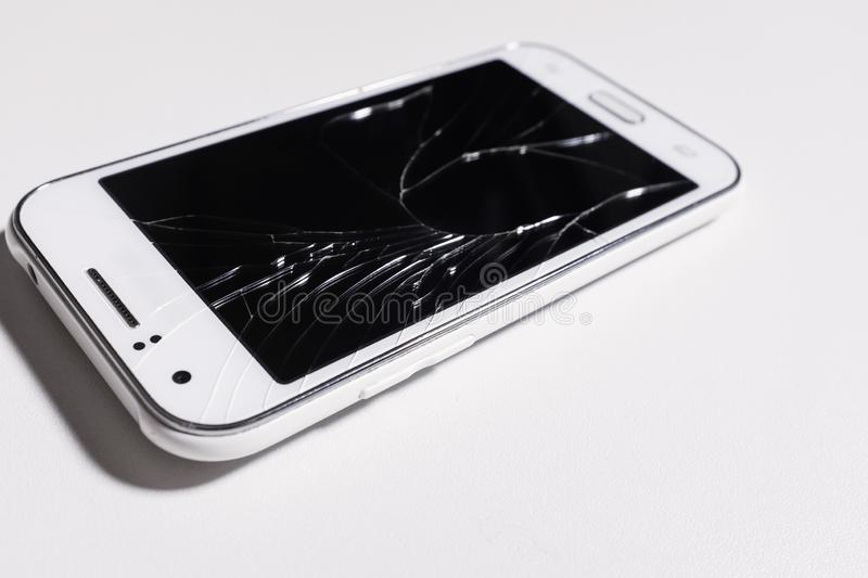 A white mobile phone is broken screen on white background.blank for copy space. isolated.  stock photo