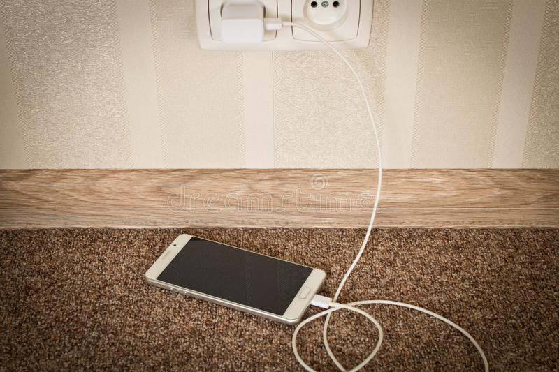 White mobile phone charging. Smartphone on charge stock image