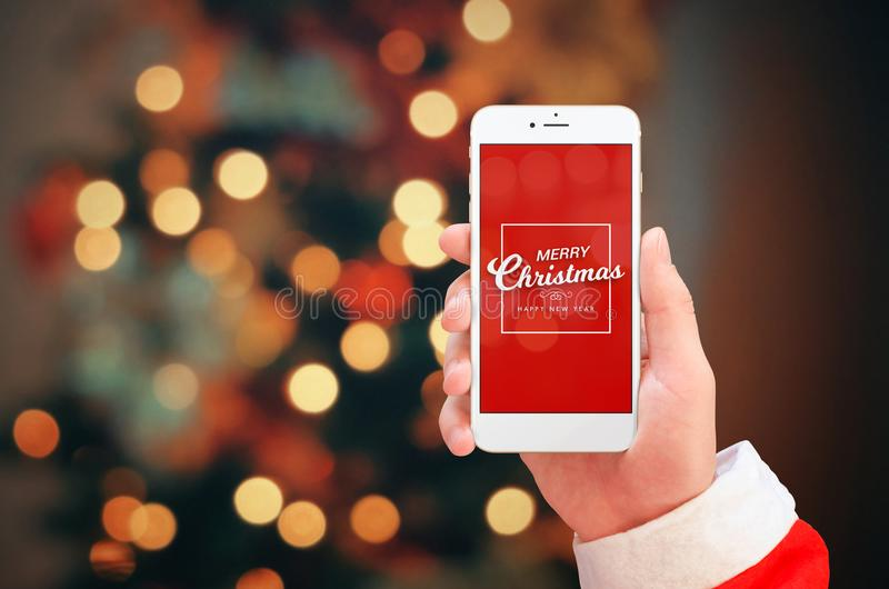 White mobile phone in Santa Claus hand close up. Merry Christmas greeting on phone display. Christmas bokeh lights in background stock photography