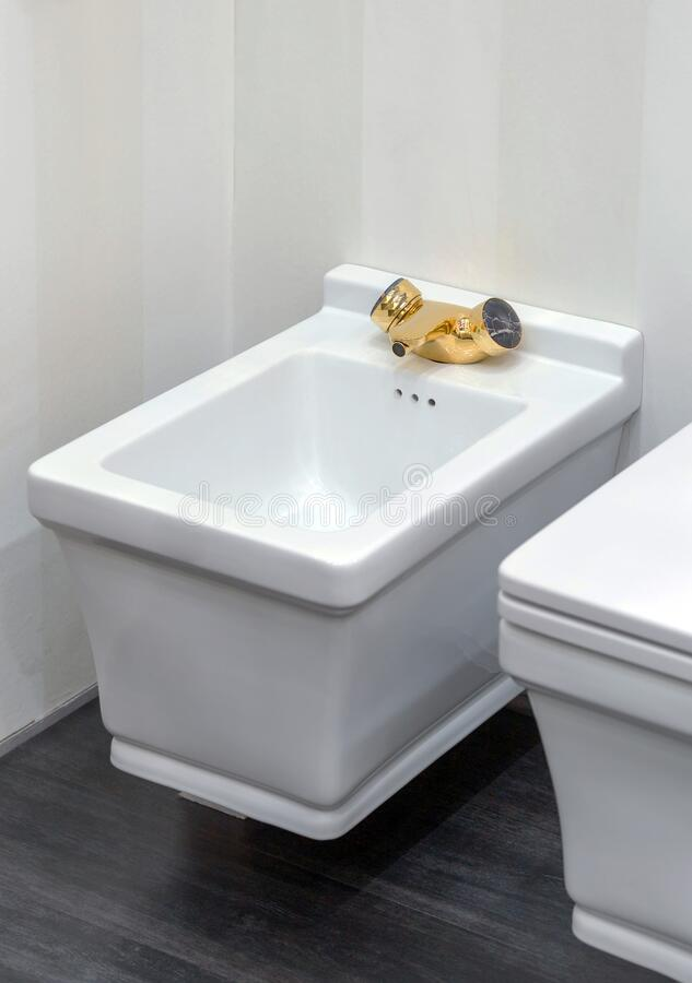 White modern bidet with gold faucet tap in light bathroom. Modern design of toilets. And bidets royalty free stock photo